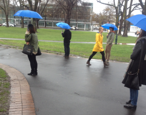 yellow coat walks through a group of blue umbrellas